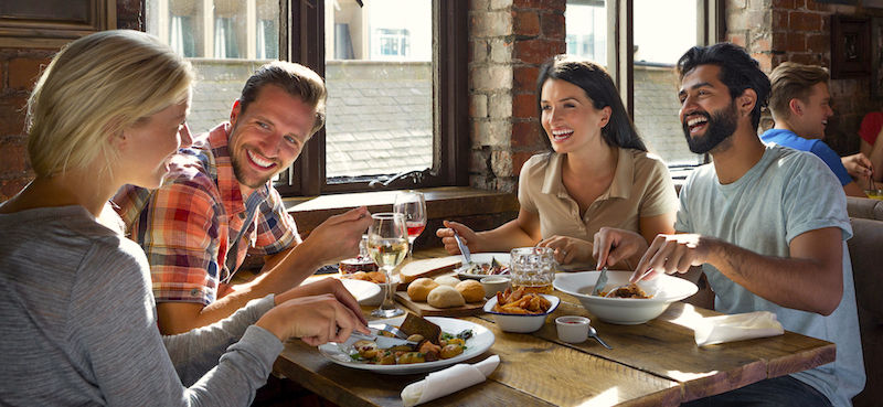 Happy customers talk and eat food at a table that features the best music for restaurants.
