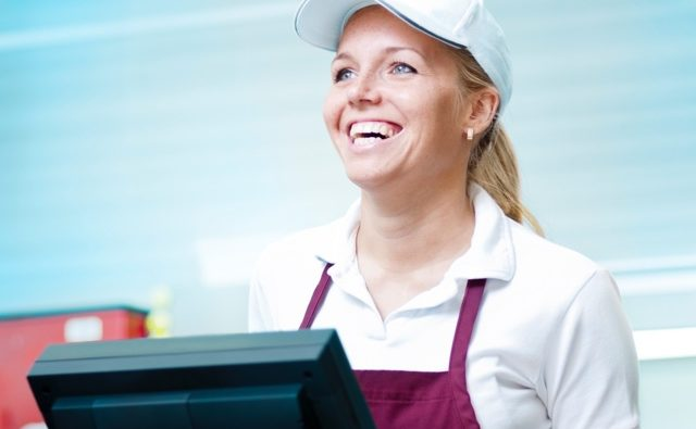 A smiling employee has a positive mood because of the upbeat restaurant music playing in the background.