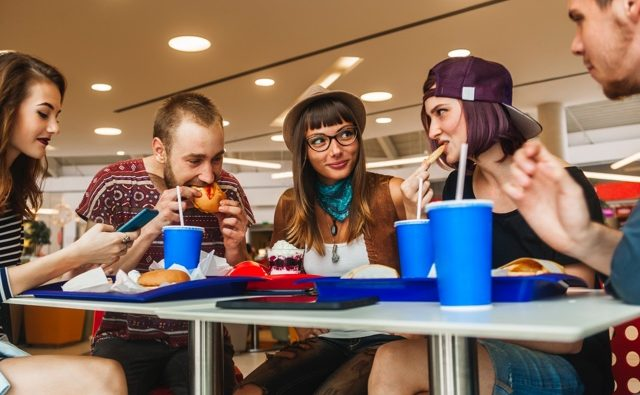 Young adults enjoy the business music as they eat at a quick service restaurant.