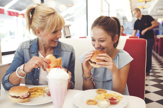 Mother and daughter site and enjoy food and music for restaurants in a quick service restaurant.