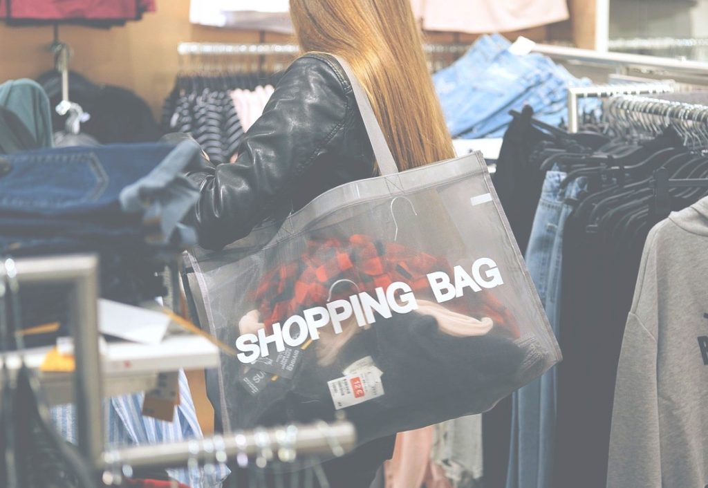 Woman shopping while listening to in store music and promotional messaging.
